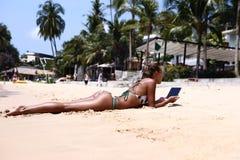 Muchacha con una tableta en la playa Imagen de archivo