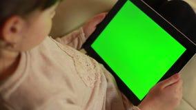 Muchacha con una tableta y una pantalla verde almacen de video