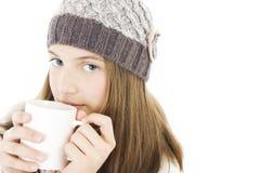 Muchacha con una taza de bebida caliente. Imagenes de archivo