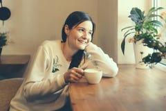 Muchacha con una taza de café en la ventana en una sonrisa de la cafetería fotografía de archivo libre de regalías