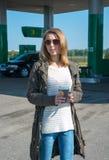 Muchacha con una taza de café en una gasolinera Fotografía de archivo