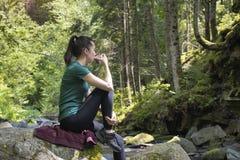 Muchacha con una taza de té que se sienta en una roca en el verano d del bosque Fotos de archivo libres de regalías
