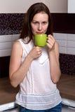 Muchacha con una taza en la cocina Fotos de archivo libres de regalías