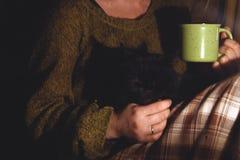 Muchacha con una taza en sus manos En las manos de un gato negro fotografía de archivo
