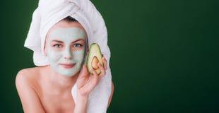 Muchacha con una toalla blanca en su cabeza con una máscara verde nutritiva en su cara y un aguacate en sus manos en un ingenio v foto de archivo