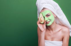 Muchacha con una toalla blanca en su cabeza con una máscara verde nutritiva en su cara y un aguacate en sus manos en un ingenio v imagenes de archivo