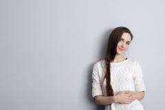 Muchacha con una trenza larga que se coloca en la pared gris y que busca Fotos de archivo