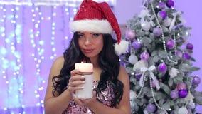 Muchacha con una vela ardiente cerca del árbol de navidad metrajes