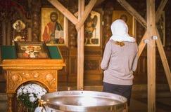 Muchacha con una vela en la iglesia ortodoxa Foto de archivo