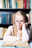 Muchacha con vista pobre que lee un libro Foto de archivo libre de regalías