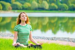 Muchacha concentrada en la posición de loto que hace yoga Foto de archivo