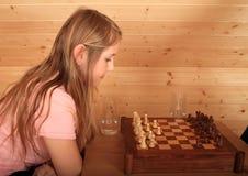 Muchacha concentrada para el próximo paso en ajedrez Imagen de archivo libre de regalías