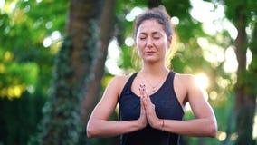 Muchacha concentrada que se coloca con las manos en namaste y que medita o que ruega Mujer joven con aspecto oriental almacen de video
