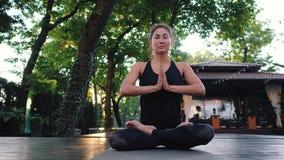 Muchacha concentrada que se sienta en actitud del loto con las manos en namaste y que medita o que ruega Mujer joven con oriental metrajes