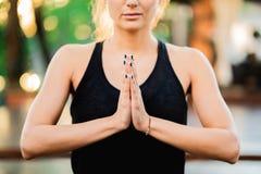 Muchacha concentrada que se sienta en actitud del loto con las manos en namaste y que medita o que ruega Mujer joven con oriental imagenes de archivo