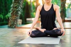 Muchacha concentrada que se sienta en actitud del loto y que medita o que ruega Yoga practicante de la mujer joven solamente en c foto de archivo