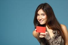 Muchacha confiada amistosa hermosa que muestra la tarjeta roja a disposición, encima Imagen de archivo libre de regalías