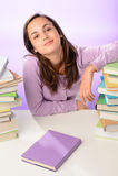 Muchacha confiada del estudiante entre las pilas de libros Foto de archivo libre de regalías