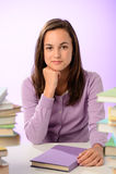 Muchacha confiada del estudiante entre las pilas de libros Imagen de archivo