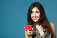 Muchacha confiada sonriente amistosa hermosa que muestra la tarjeta roja en la ha Foto de archivo