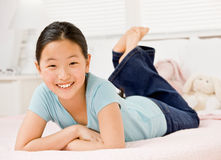 Muchacha confidente que pone en cama en dormitorio Imagenes de archivo