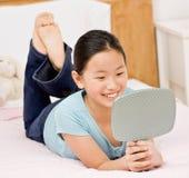 Muchacha confidente que pone en la reflexión de la visión de la cama Imagen de archivo