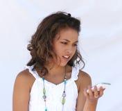 Muchacha confundida con el teléfono celular. Imagenes de archivo