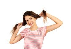 Muchacha confundida con su pelo muchacha emocional aislada en el fondo blanco foto de archivo