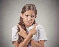 Muchacha confusa del adolescente que señala en dos diversas direcciones Foto de archivo libre de regalías