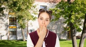 Muchacha confusa del estudiante que cubre su boca a mano Imagen de archivo