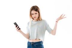 Muchacha confusa joven que sostiene el teléfono móvil y que encoge hombros Fotografía de archivo