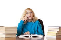 Muchacha contemplativa de la escuela que se sienta en el escritorio Imagen de archivo libre de regalías