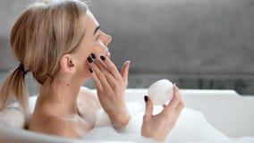 Muchacha contenta feliz que goza aplicando la crema de cara para alisar el primer puro de la piel de la cara en cuarto de baño almacen de video