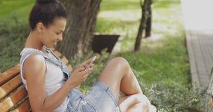 Muchacha contenta que usa smartphone en parque Fotos de archivo libres de regalías