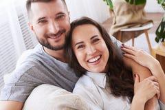 Muchacha contenta y muchacho que abrazan y que se relajan en el sofá Fotografía de archivo libre de regalías