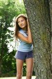 Muchacha contra un árbol Foto de archivo