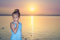 Muchacha contra una puesta del sol rosada sobre el lago de sal Fotografía de archivo