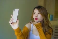 Muchacha coreana asiática atractiva y relajada joven usando dormitorio del teléfono móvil en casa que goza del app que fecha en l fotos de archivo libres de regalías