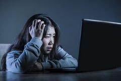 Muchacha coreana asiática preocupante del estudiante que mira el estudiar presionado y desesperado con el ordenador portátil en l Imagen de archivo