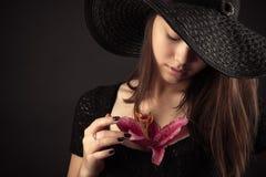 Muchacha coreana del adolescente con la flor del lirio aislada en negro Fotos de archivo libres de regalías