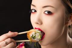 Muchacha coreana hermosa del adolescente con maquillaje brillante que come el sushi Foto de archivo