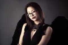 Muchacha coreana joven con las alas negras fotos de archivo
