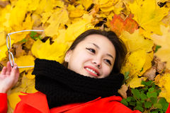 Muchacha coreana sonriente con los vidrios que mienten en las hojas Fotografía de archivo libre de regalías