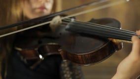 Muchacha creativa en el vestido negro que toca el violín encendido almacen de video