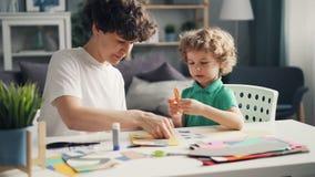Muchacha creativa y su niño elegante que hacen el collage de papel que crea hermoso diseño almacen de metraje de vídeo