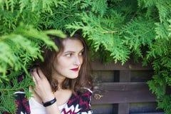Muchacha cubierta con las ramas de árbol verdes delante de la cerca de madera Foto de archivo libre de regalías
