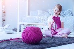 Muchacha curiosa elegante que hace punto la bufanda caliente en casa Fotografía de archivo libre de regalías