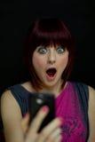 Muchacha dada una sacudida eléctrica en el mensaje de texto en el teléfono celular Fotos de archivo