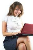Muchacha dark-haired joven hermosa que pulsa en la computadora portátil Fotografía de archivo