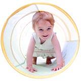 Muchacha de 2 años que se arrastra en un túnel Fotos de archivo